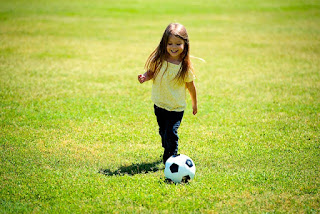 image young girl playing soccer in field alone