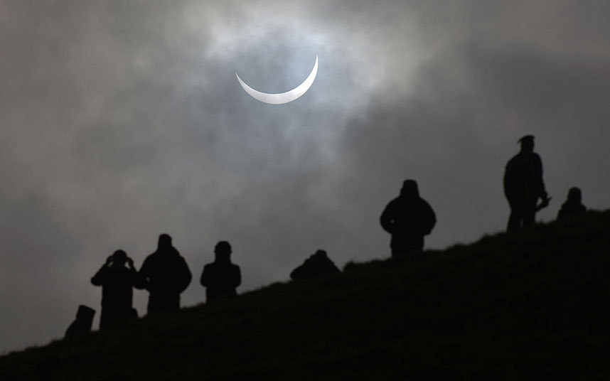 People gather at Glastonbury Tor to watch the eclipse.