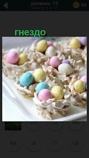 цветные яйца на пасху лежат в сделанных гнездах