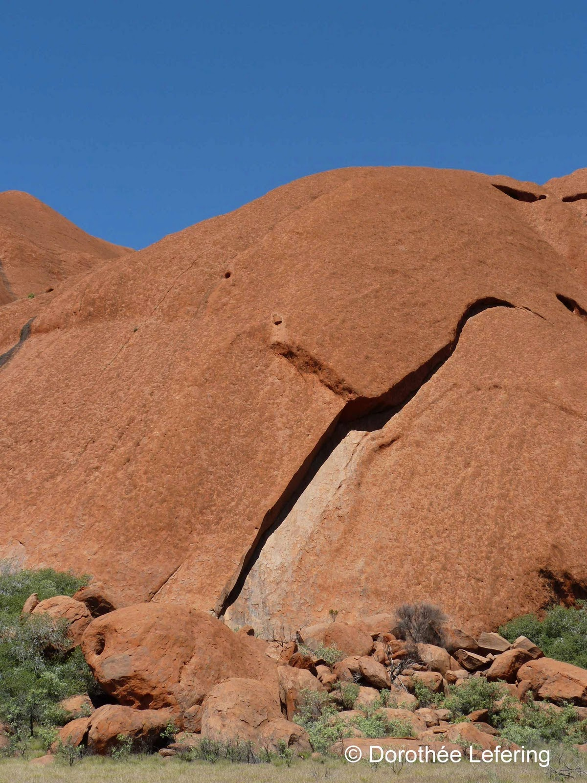 Massive red rock formations under a bright blue sky in Australia..