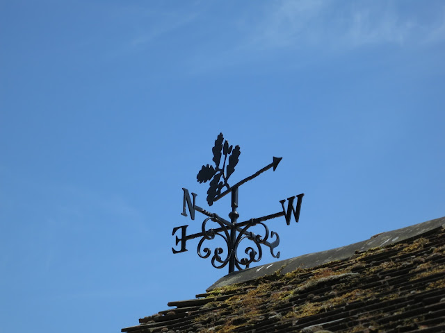 Metal weathervane with oak leaf symbol on top of tiled roof with moss.