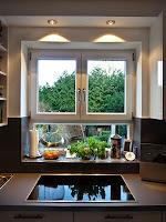 Auf Wunsch der Kundin wurde das Kochfeld direkt vor das Fenster gesetzt, damit sie beim Kochen in ihren schönen Garten schauen kann