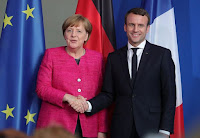 Merkel and Macron (Photographer Credit: Krisztian Bocsi/Bloomberg) Click to Enlarge.