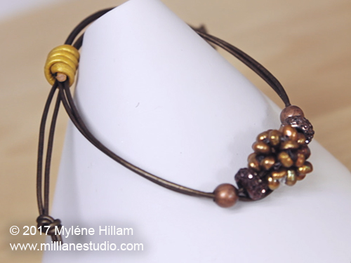 Adjustable bracelet with sliding knot on a brown leather cord, strung with copper freshwater-pearl cluster beads.