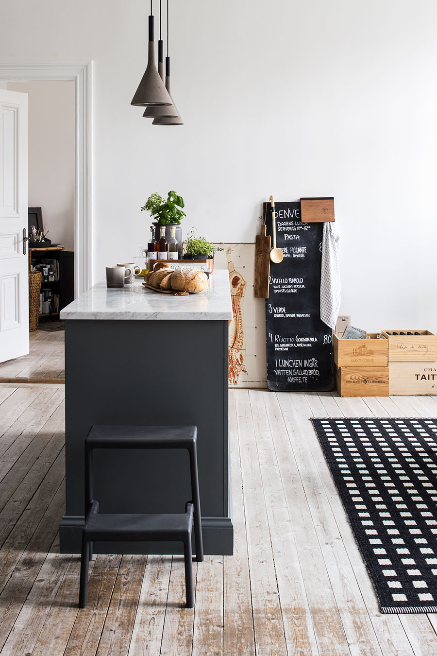 Dark gray kitchen, concrete lamp, black and white carpet, wooden boxes