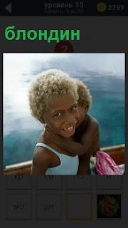 Мальчик с черным цветом лица, но белые волосы как у блондина, на руках держит ребенка