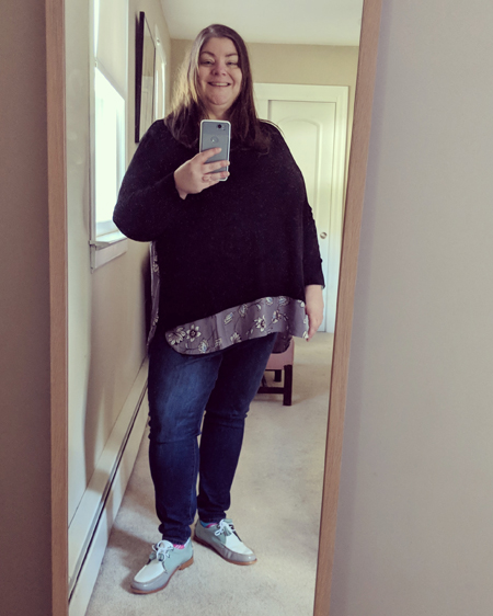 image of me, a fat, white, middle-aged woman with long brown hair, standing in a full-length mirror wearing a mixed media black and lavender-patterened top, blue jeans, and lavender, teal, and white patent oxfords