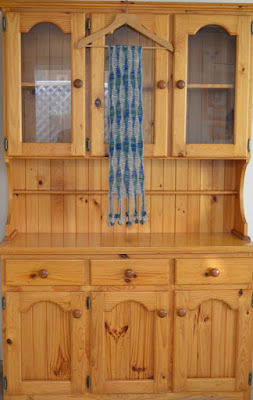 Full length photo of dining room dresser; clear laquered pine which has darkened with age; three doors wide; the buffet below has three solid doors and the hutch above has three glass doors.  Hanging on a coathanger from the top of the dresser is the latest silk mohair scarf in wavy blue-green and silver grey patterns.
