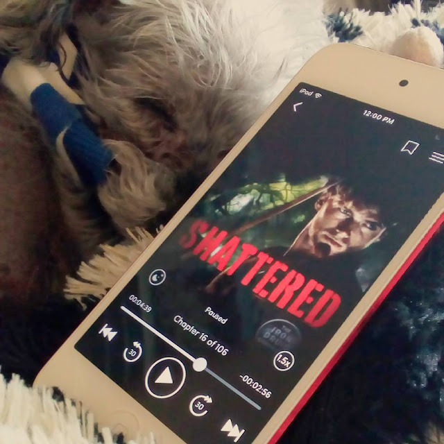 Murchie sleeps curled up behind a white iPod with Shattered's cover on it. The cover features a redheaded white man holding a sword.