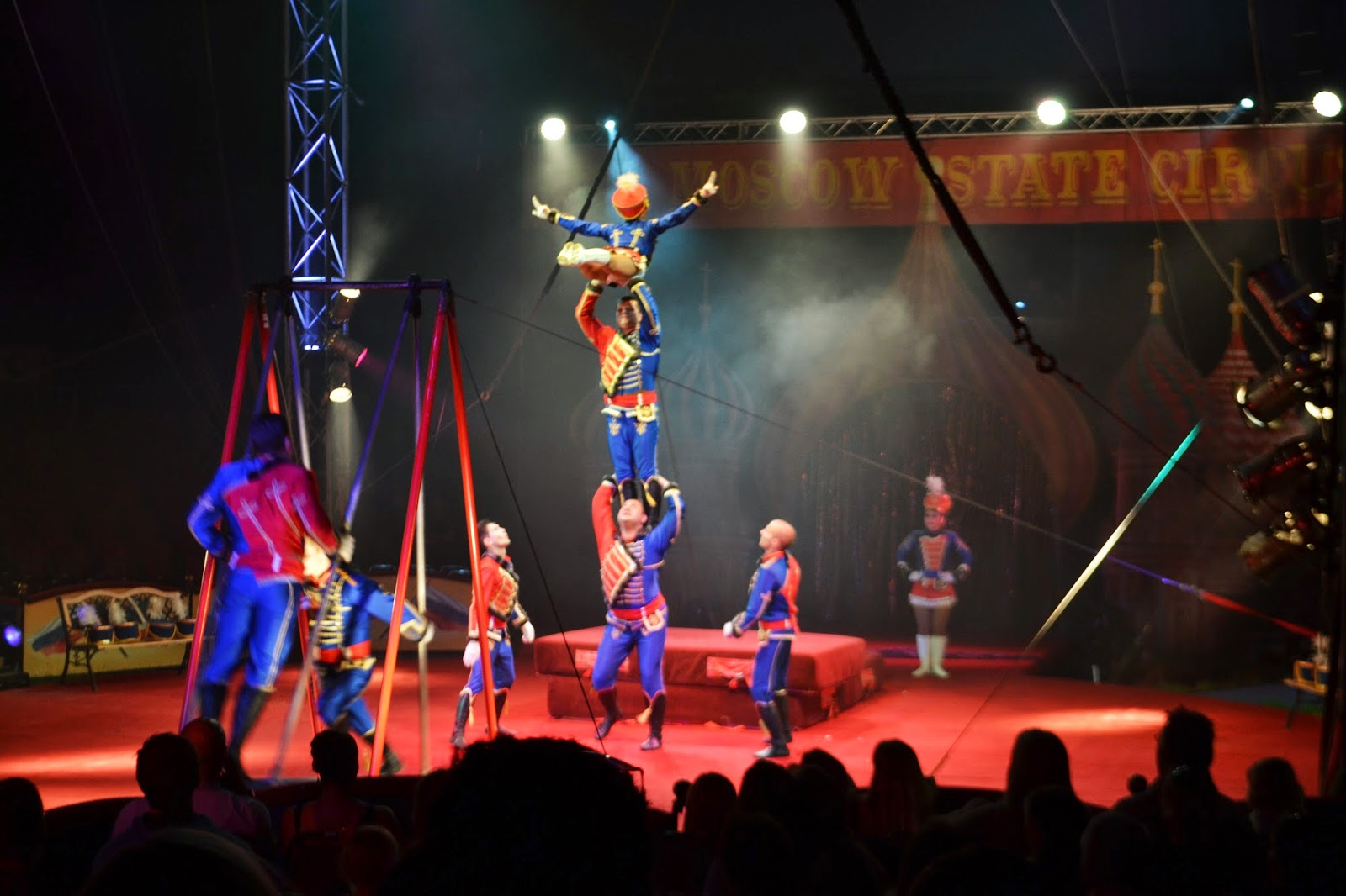 a group of circus actors climbing to stand on top of each other to create a human tower