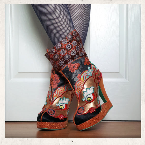 wearing Irregular Choice Tatsu dragon ankle boots in orange and blue
