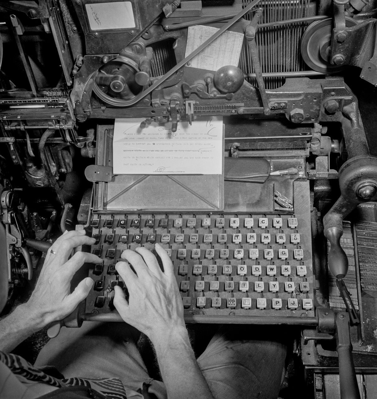A linotype operator types out a story in the composing room. The linotype is used to cast metal blocks of type which will then be laid out into a page.