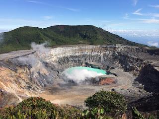 Imagen desde arriba de la laguna del volcán, con agua de color azul intenso y una leve fumarola que sale de ella