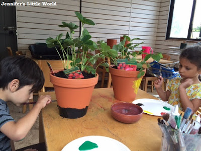 Painting strawberry planters at the garden centre