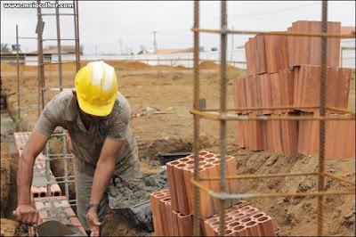 pedreiro levantando parede de tijolos