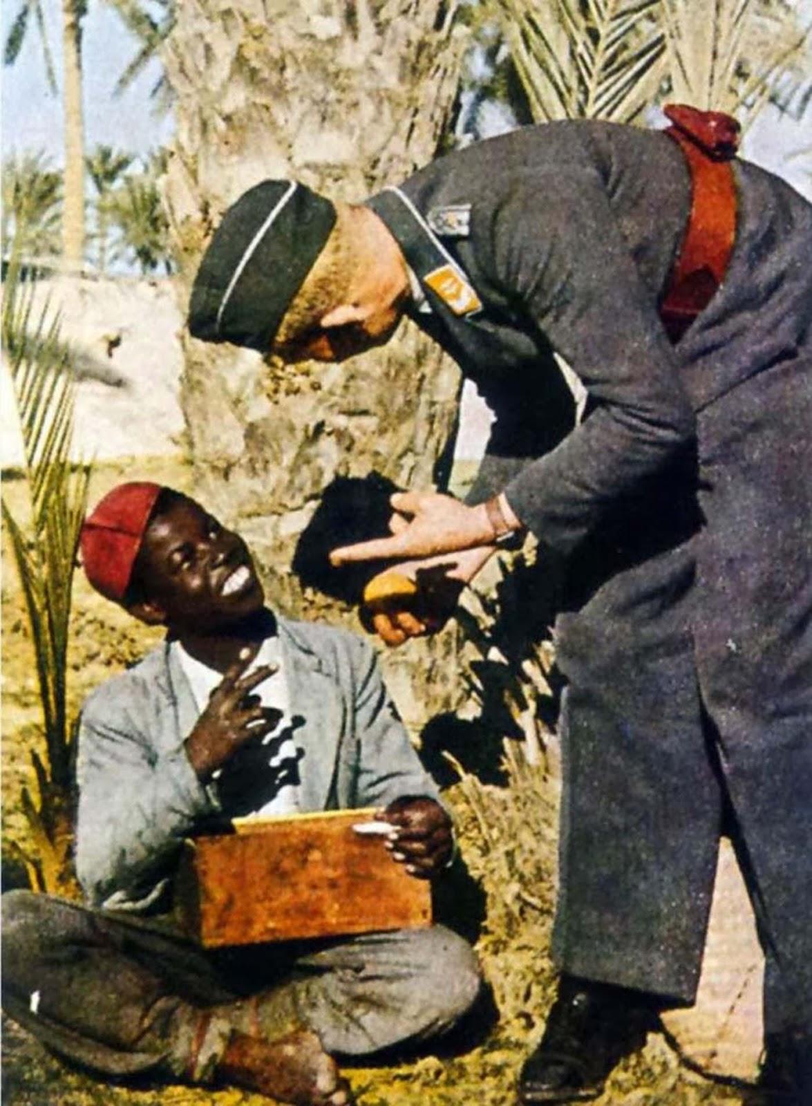 Un miembro de la Luftwaffe intercambia regalos con un nativo en el norte de África, 1941.