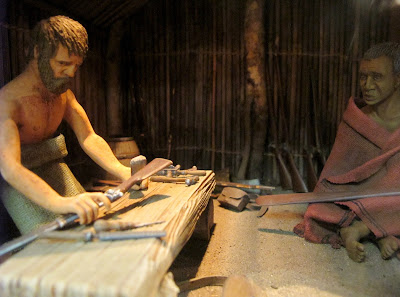 A full-sized diorama of a pakeha man and a Maori man in a Maori hut. The pakeha is working on agun.