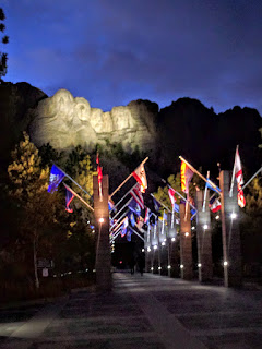 Mount Rushmore, South Dakota, and flags at night