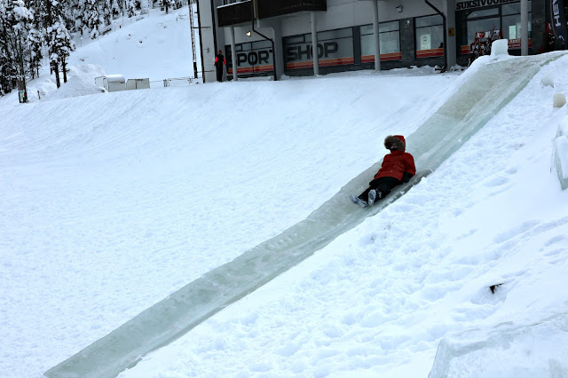 Boy sliding down a purpose-built ice slide in a hill.