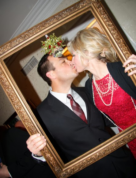 Mistletoe hangs from this vintage frame that guests used for a creative wedding photo booth