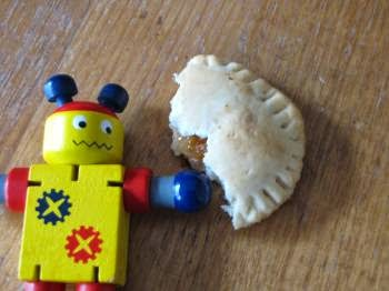 Un piccolo robot giocattolo accanto a un biscotto