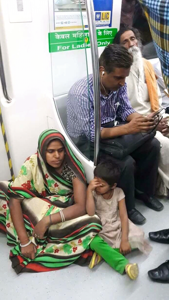 In delhi metro, woman seat on floor while man seat on the seat