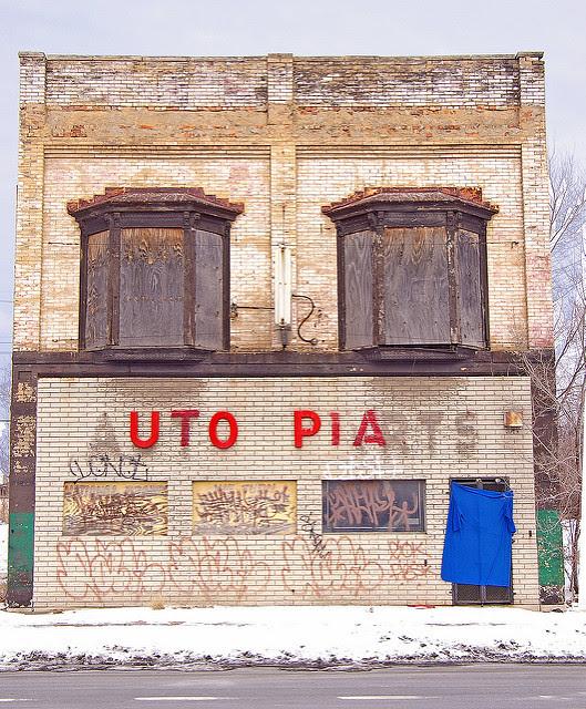 """Antic edifici de recanvis d'automòvil abandonat i una mica vandalitzat on el rètol de """"Auto Parts"""" ha estat modificat per que es pugui veure """"Utopia"""""""