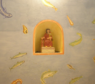 Bath house wall painted with fish and goddess statue in niche
