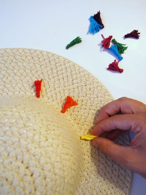 Add tassels to a simple straw hat for a bit of colorful summer fun! via @mvemother