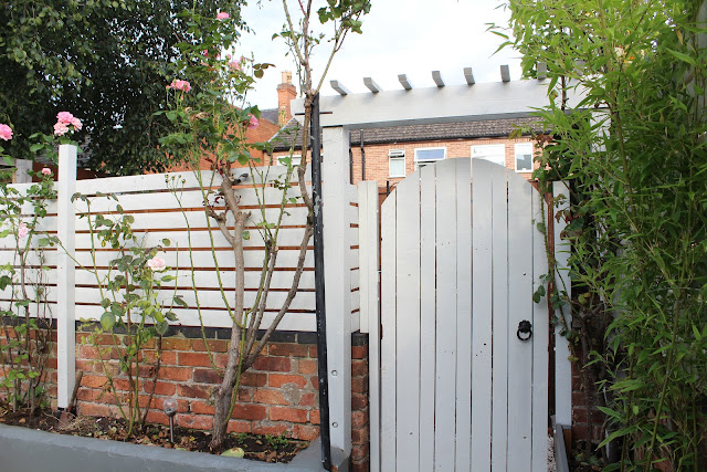 slat fencing with pergola over gate