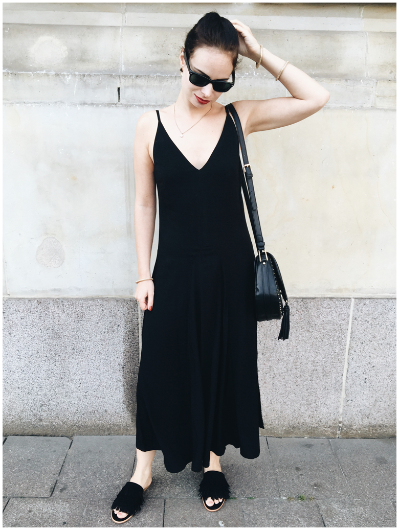 #ALLBLACKEVERYTHING | June Gold wearing a black & Other Stories dress and black & Other Stories fringed slip-on sandals