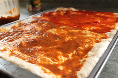 Raw pizza dough topped with sauce