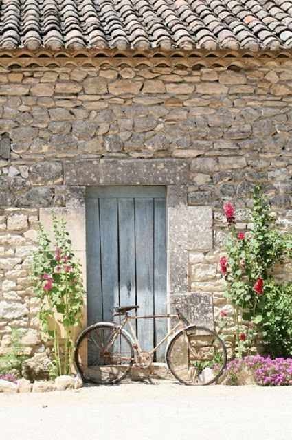 Stone French farmhouse exterior with clay roof and vintage bicycle on Hello Lovely Studio