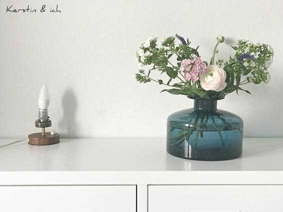 Frühlings-Blumenstrauß in blauer Vintage-Glasvase