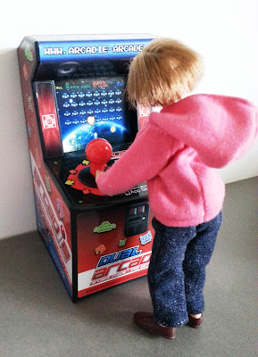 Modern dolls' house miniature arcade game, being played by a doll wearing jeans and a hoodie.