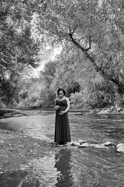 a stunning black and white photograph of a pregnant woman in a long gown along a creek in colorado