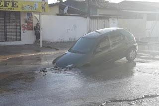 Asfalto cede e cratera formada por vazamento de água engole parte de carro em Mangabeira