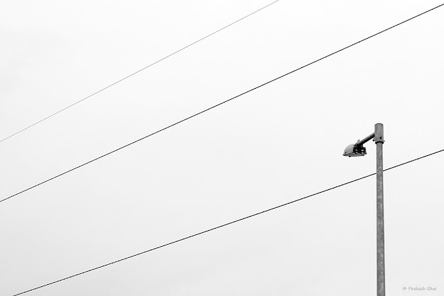 A Black and White Minimalist Photo of a Street Lamp and Three wires in the Sky