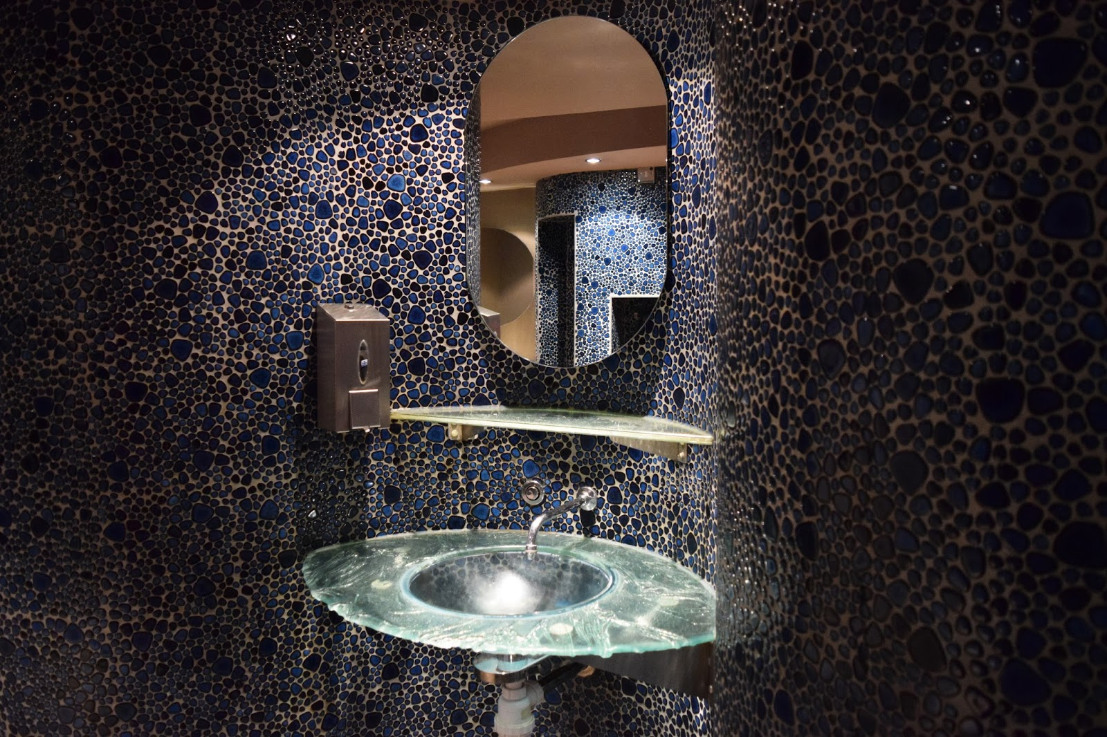 the sink area of a pub toilet. the walls are covered in blue mosaic stones