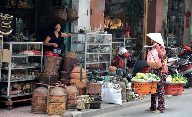 """Đối diện chợ Bến Thành là con phố được người ta gọi là """"chợ"""", dẫu không sầm uất, ồn ào, náo nhiệt so với chợ thông thường, nhưng con phố ấy đầy hấp lực với người hoài cổ, bởi là nơi tập trung buôn bán cổ vật lớn nhất nước, trong đó gốm sứ mang niên đại từ cổ chí kim là một mảng hiện vật hấp dẫn và giá trị nhất ở """"chợ Kiều"""".        Con đường Lê Công Kiều – chợ Kiều – cũng là con đường hiếm hoi ở Sài Gòn từng đón các chính khách quốc tế, từ tổng thống, thủ tướng, đến thái tử… mỗi dịp công du Việt Nam, thường dành chút thời gian dạo chợ, bởi đó là nơi có thể khám phá thêm những nét lạ về văn hóa, con người Việt Nam thông qua các hiện vật bày bán, đặc biệt là gốm sứ."""