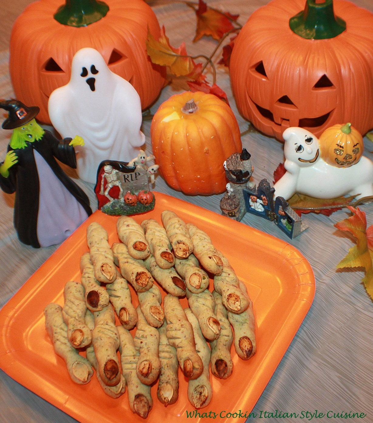 This are pistachios cookies molded into witches fingers for a Halloween party with a witch, ghost, pumpkins on an orange plate