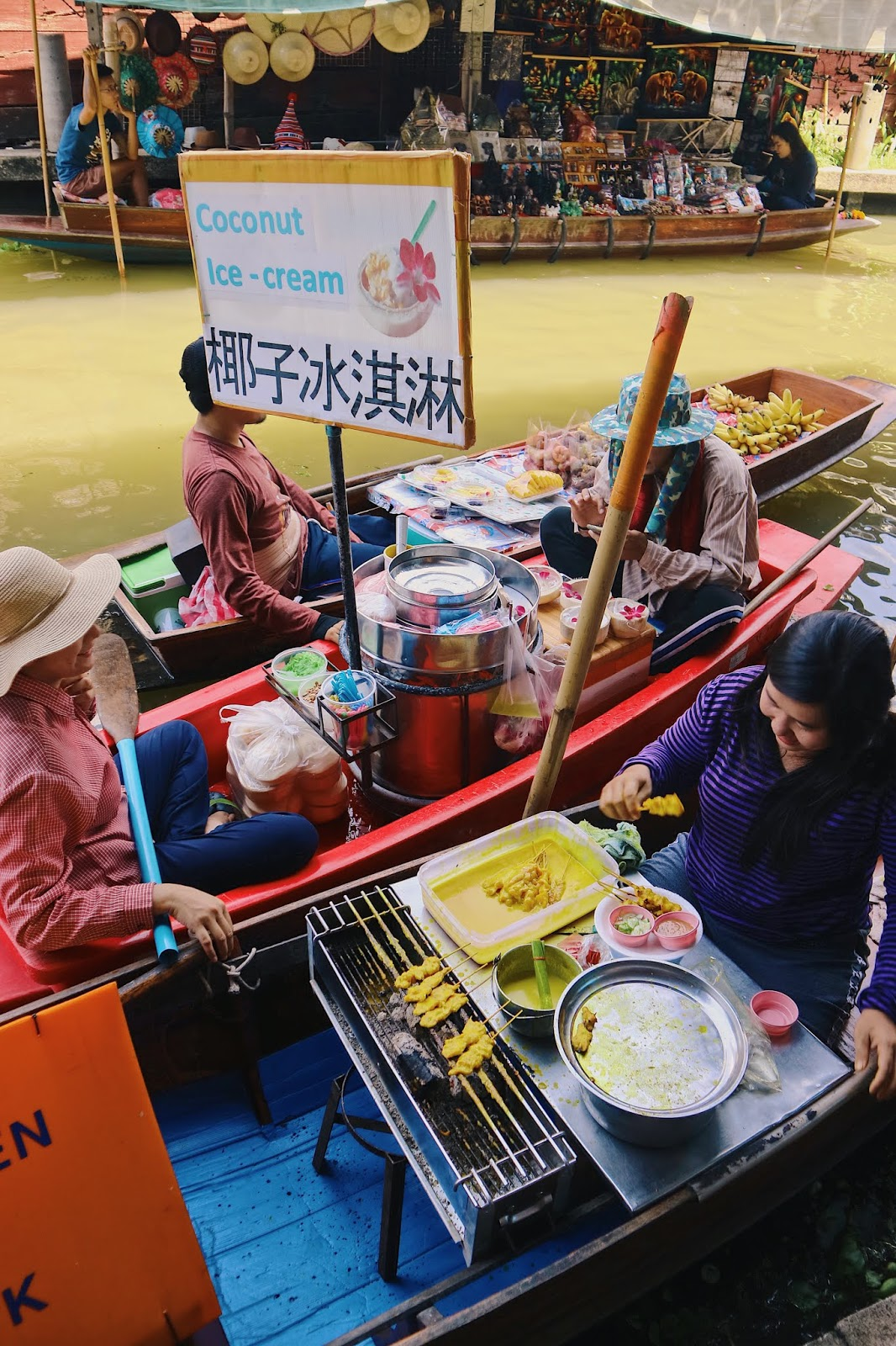coconut ice cream and satay for sale at Damnoen Saduak Floating Market