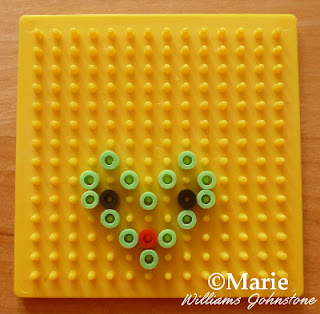 Yellow peg board with different color beads