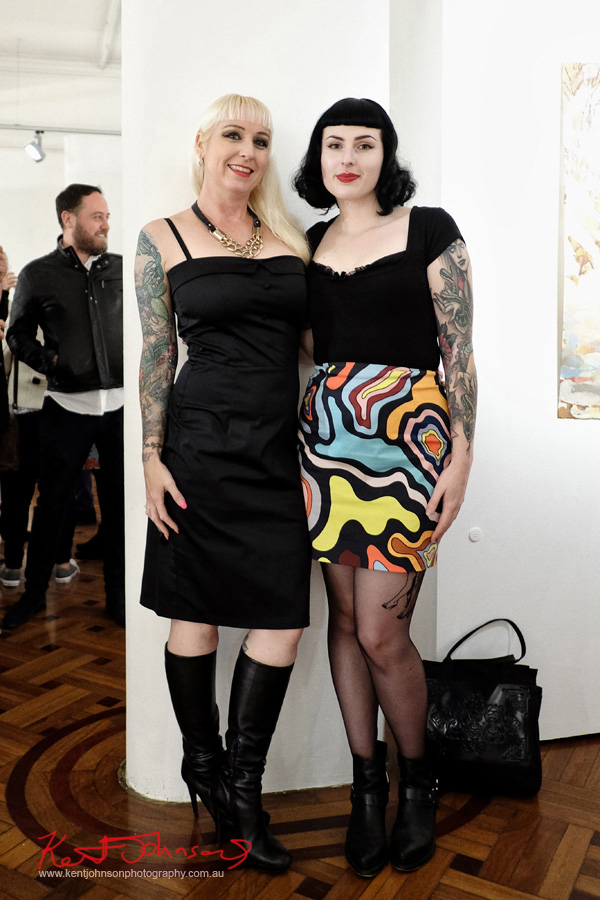 Hot girls with off-duty burlesque style, tattoos, black boots, black dress, print skirt black top. Photos by Kent Johnson for Street Fashion Sydney.