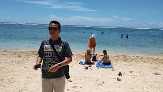 Wawan dengan latar turis yang berjemur di Pantai Pandawa Bali