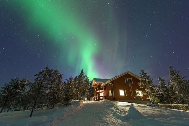 Aurora boreal sobre chalé e pinheiros em Ivalo, Finlândia
