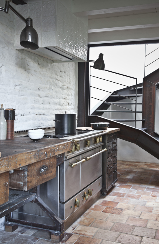 A pair of industrial sconces couldn't miss from the amazing statement kitchen in Isis-Colombe Combréas summer house