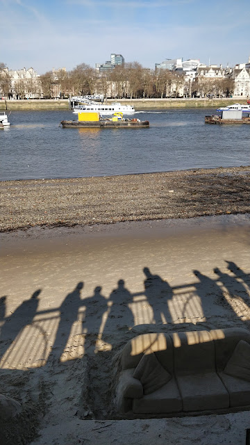 shadows of people admiring sand art along the Thames