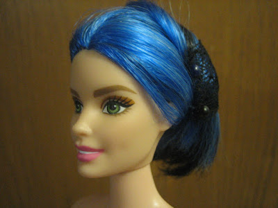 Curvy Barbie's blue and black hair up in a bun