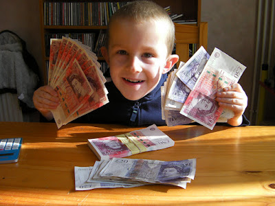 boy holding five thousand cash in £50 notes
